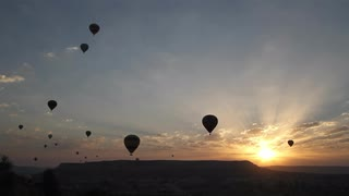 wide-shot-of-silhouetted-hot-air-balloons-drifting-in-the-sky-at-sunrise_4dmpsu3og__S0000